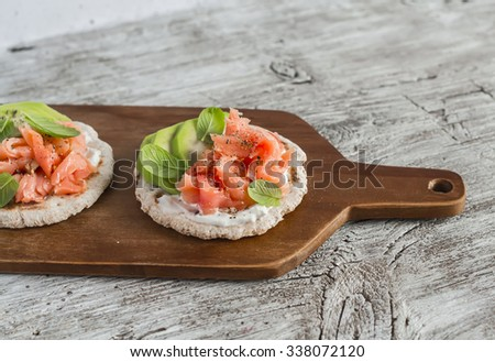 Whole grain tortilla with avocado and salmon, served on a wooden board, bright wooden surface. Rustic style. Healthy food - stock photo