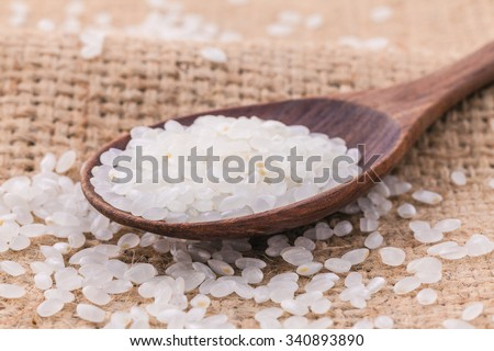 Whole grain traditional japanese rice  in wooden spoon with hemp sacks background - stock photo
