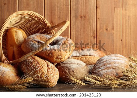 Whole grain wheat bread in basket with wheat ears. - stock photo