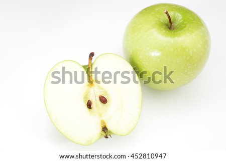 whole green apple and half with leaf isolated