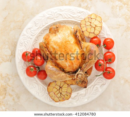 whole grilled chicken on a plate with tomatoes and garlic. top view - stock photo