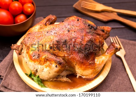 Whole grilled chicken on wooden plate - stock photo