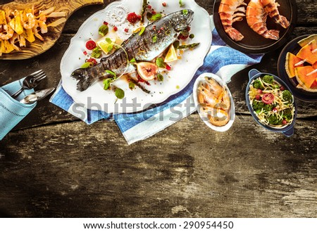 Whole Grilled Fish on White Platter Surrounded by Seafood Dishes on Rustic Wooden Table with Linen Napkins and Cutlery with Copy Space - stock photo