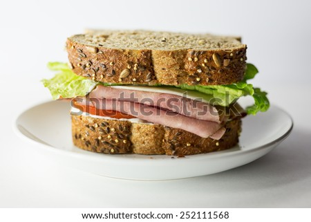 Whole ham and cheese sandwich on organic five grain bread with lettuce, tomato and mayonnaise.  Presented on a white plate, white background.  - stock photo