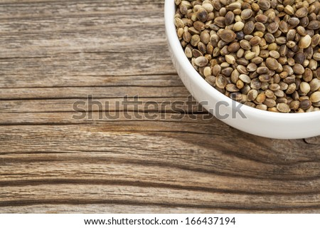 whole hemp seeds in a small bowl on a grained wood - stock photo