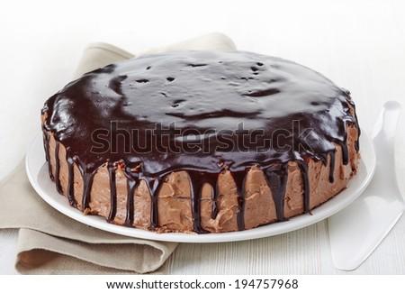 Whole homemade chocolate cake on white wooden background - stock photo