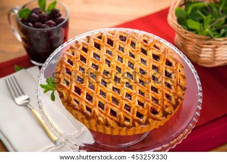Whole homemade fresh black cherry pie tart golden crust fruit filled delicious dessert - stock photo