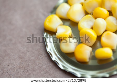 Whole kernel sweet corn on the tin can. Paper craft background. soft focus, macro view. - stock photo