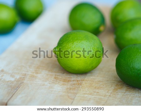 Whole limes closeup on wooden cutting board