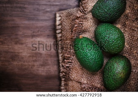 Whole organic avocado on a dark wood background / selective focus, copy space - stock photo