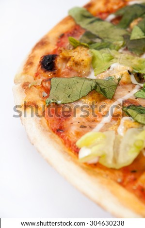 Whole pizza with lettuce on a white background.