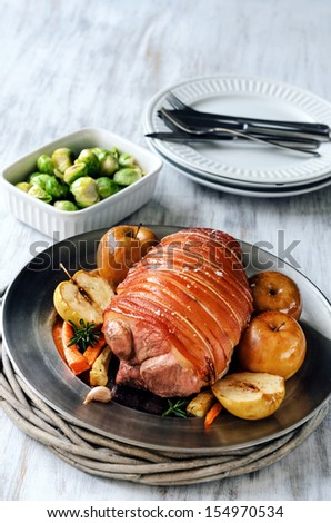 Whole pork shoulder roast with apple and vegetables, served on a table, traditional sunday lunch  - stock photo