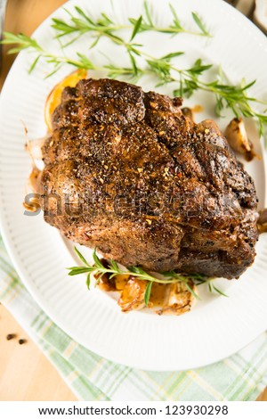 Whole Pot Roast Ready for Serving with Vegetables and Fresh Herbs - stock photo