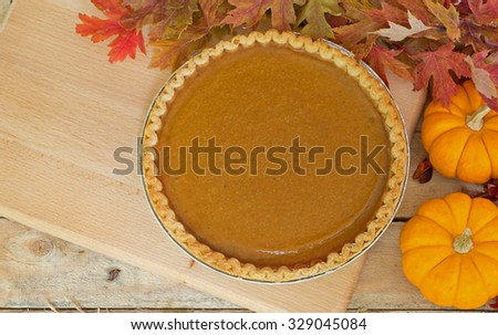Whole pumpkin pie with autumn leaves and pumpkins - stock photo