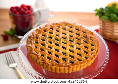 Whole raspberry mixed berry pie tart served on a table perfect golden brown crust