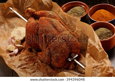 Whole raw chicken with spices ready for roasting on a spit - stock photo