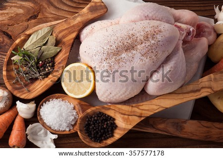 Whole raw chicken with vegetables and pepper - stock photo