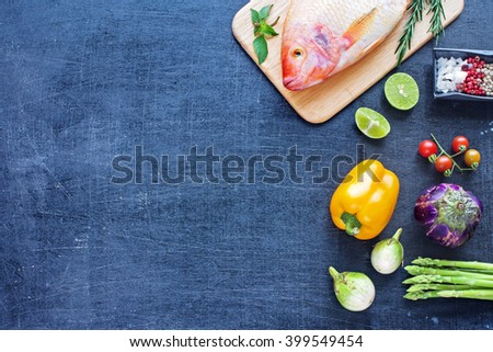 Whole raw fish (Nile tilapia) with herbs and spices. Fresh vegetables (asparagus, eggplant, bell pepper, cherry tomato). Dark background. Copy space. - stock photo