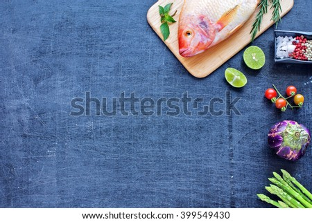 Whole raw fish (Nile tilapia) with herbs and spices. Fresh vegetables (asparagus, eggplant, cherry tomato). Dark background. Copy space. - stock photo