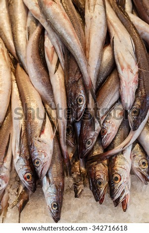 Whole raw fish on ice at a sidewalk market - a tasty food and deadly food allergen. - stock photo