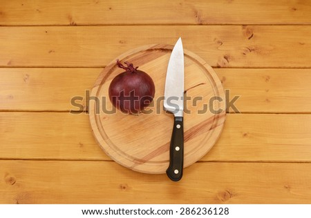 Whole raw red onion with a sharp kitchen knife on a wooden chopping board - stock photo