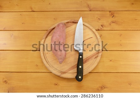 Whole raw sweet potato with a sharp kitchen knife on a wooden chopping board - stock photo