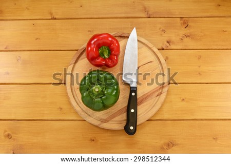 Whole red and green peppers with a sharp kitchen knife on a wooden chopping board  - stock photo