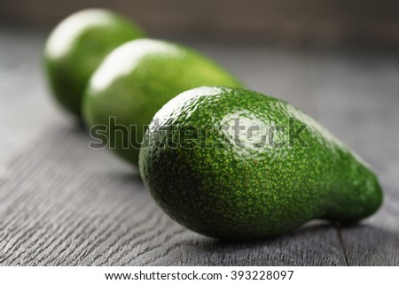 whole ripe green avocados on wood table, selective focus