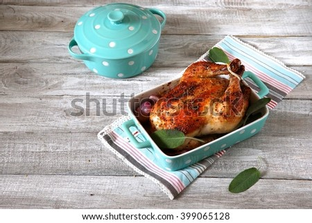 Whole roast chicken on grey background with blue pot - stock photo