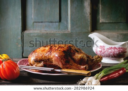 Whole roast honey duck with meat fork in vintage plate, served with fresh vegetables and porcelain gravy boat over old wooden table. - stock photo