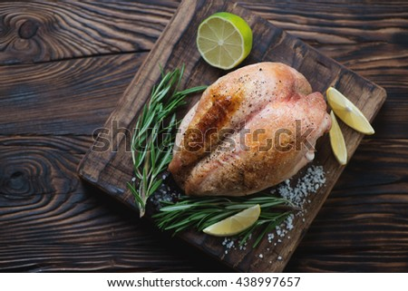 Whole roasted chicken breast, rustic wooden setting, top view