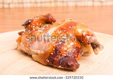 Whole roasted chicken dish wood on wooden table
