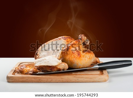 Whole roasted chicken on wooden board with a cut