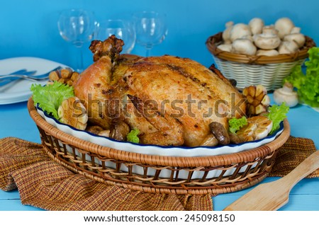 Whole roasted chicken stuffed with buckwheat and mushrooms on a blue background - stock photo