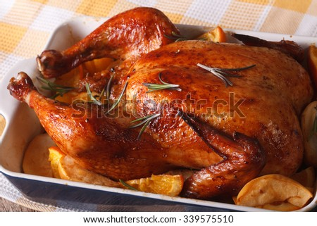 Whole roasted chicken with apples and oranges in the baking dish on a table close-up. horizontal