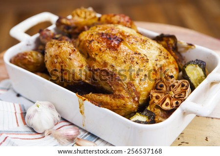 Whole roasted chicken with garlic, potatoes and vegetables in a white ceramic roasting pan - stock photo