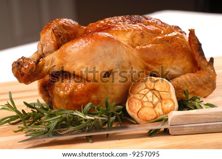 Whole roasted chicken with garlic, rosemary and carving knife