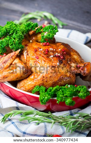 Whole Roasted Chicken with herbs and tomatoes over wooden background