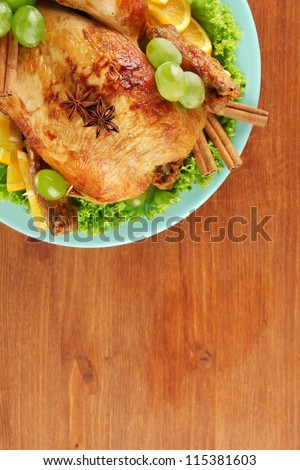 whole roasted chicken with lettuce, grapes, oranges and spices on blue plate on wooden background close-up