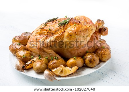 Whole Roasted Chicken with New Potatoes, Mushrooms, Lemon Wedges and Garlic Cloves - stock photo