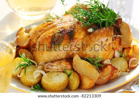 Whole roasted chicken with potatoes and provencal herbs - stock photo