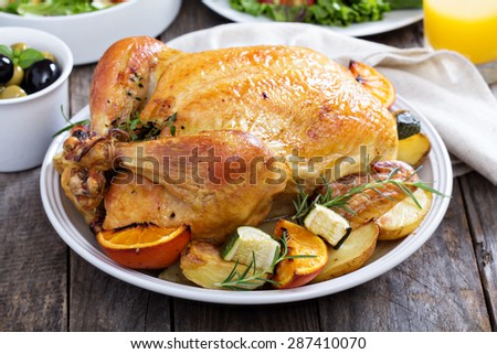 Whole roasted chicken with potatoes on dinner table - stock photo