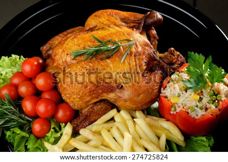 Whole roasted chicken with vegetables and rosemary - stock photo