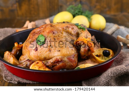 Whole roasted chicken with vegetables on pan, on wooden background - stock photo