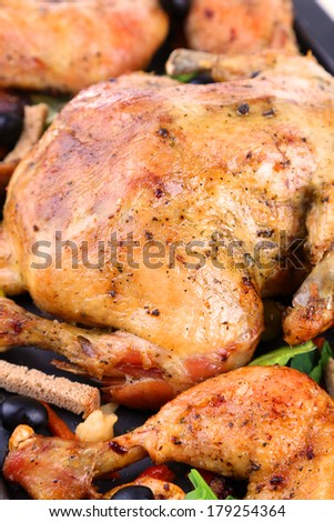 Whole roasted chicken with vegetables on tray, close-up