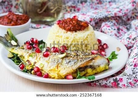 Whole roasted Dorado fish with couscous, pomegranate, herbs and tomato sauce, Arabic dish - stock photo