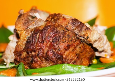 Whole roasted pork, green wild onion and carrot on yellow-orange background