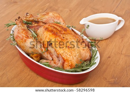 whole roasted stuffed turkey  in a dish with gravy - stock photo