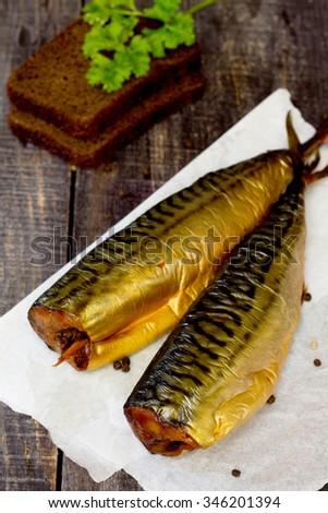 Whole smoked fish (mackerel) on a dark wooden table - stock photo