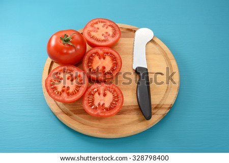 Whole tomato and four cut halves with a tomato knife on a wooden cutting board